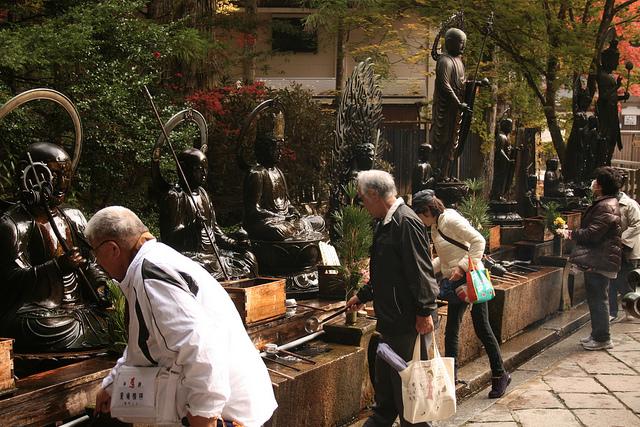 Imagen de peregrinos mojando a los budas con agua sagrada en el cementerio de Okunoin